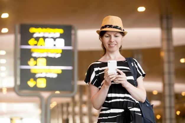 mujer-con-un-telefono-inteligente-en-el-aeropuerto_1163-708